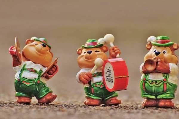 imagen de tres esculturitas de osos alegres caracterizados como músicos suizos